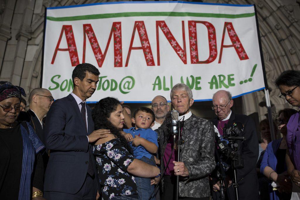 """Amanda Morales sostiene a su hijo, David, durante una conferencia de prensa sobre su decisión de tomar refugio en la Iglesia de Holyrood. Está flanqueada por líderes interreligiosos y por el concejal de la ciudad de Nueva York, Ydanis Rodríguez. """"Ha sido muy difícil refugiarse, vivir como un prisionero que no puede salir de la iglesia sin el riesgo de ser deportado"""", dice Amanda. """"Además, uno no está preparado para dar entrevistas y hablar con periodistas. Mis hijos son siempre preguntando: """"¿Por qué, mami? ¿Por qué?"""" Manhattan, Nueva York, Estados Unidos. 27 de septiembre de 2017."""