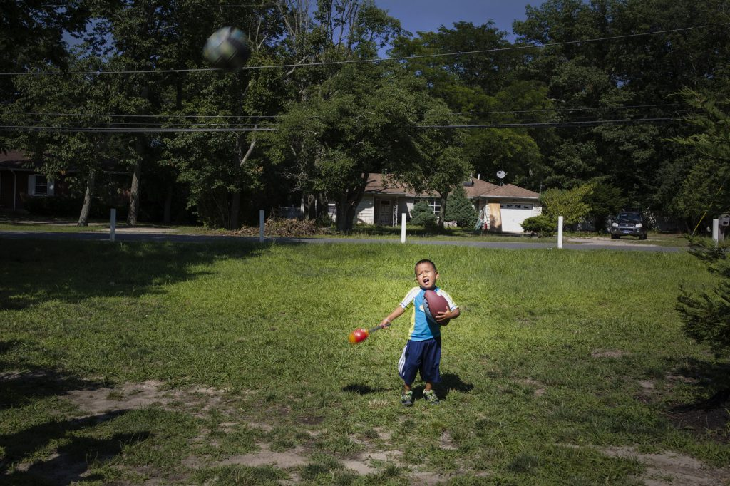 Portrait of Juan playing soccer at his house in New Jersey, a few days after being reunited with his mother, Betty. New Jersey, United States, 2018.