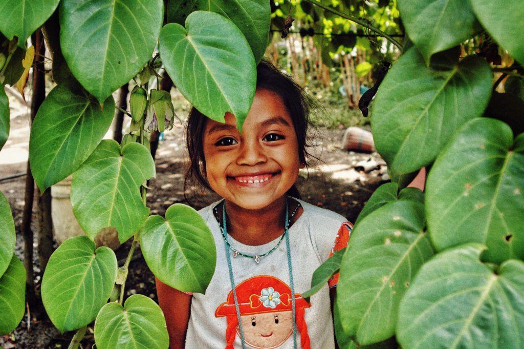 Silvia posa bajo la planta de chayotes en la casa de sus abuelos en uno de los múltiples viajes que realizó de vuelta a su pueblo con su familia.